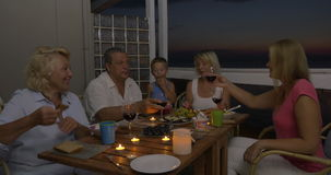 Family having meal on balcony in the evening stock footage