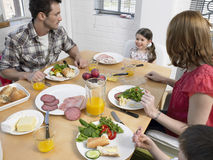 Family Having Meal At Dining Table. Family of four having meal together at dining table in kitchen stock photography