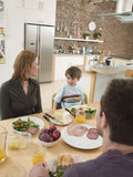 Family Having Meal At Dining Table. Happy parents with son having meal at dining table in kitchen stock photo