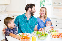 Family having meal in kitchen. Happy family talking to each other while having meal in kitchen at home Stock Photography
