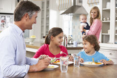 Family Having Meal In Kitchen Together Stock Photos