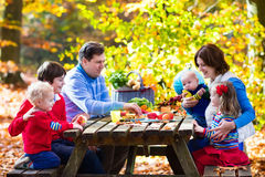 Family having picnic in autumn. Happy young family with four children grilling meat and making sandwich and salad on a picnic table in sunny autumn park Royalty Free Stock Photography
