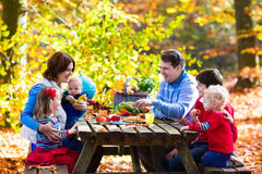 Family having picnic in autumn. Happy young family with four children grilling meat and making sandwich and salad on a picnic table in sunny autumn park Royalty Free Stock Photos