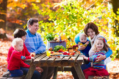 Family having picnic in autumn. Happy young family with four children grilling meat and making sandwich and salad on a picnic table in sunny autumn park Royalty Free Stock Image