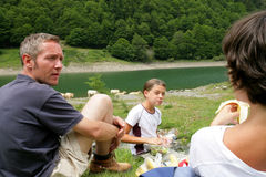 Family having a picnic in the mountains. Father mother and daughter sitting on the grass, having a picnic Stock Photo
