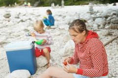 Family having a picnic in nature out of a cool box. Outdoor lifestyle, positive parenting, childhood experience concept. Family having a picnic in nature out of royalty free stock photography