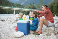 Family having a picnic in nature out of a cool box, sitting on the river bank royalty free stock photo