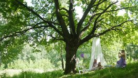 Family having picnic in park - father, mother and daughter under big tree stock footage