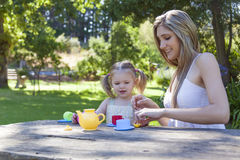 Family having picnic in summer park. And pretend tea party Royalty Free Stock Images