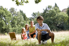 A family having a picnic, young boy sitting on a football Stock Images
