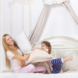 Family having pillow fight in a bedroom Royalty Free Stock Images