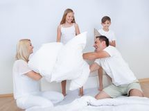 Family Having A Pillow Fight Together On Bed Stock Photos