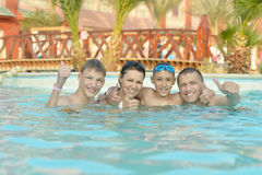 Family having  in pool. Happy family having fun in pool with thumbs up Royalty Free Stock Photography