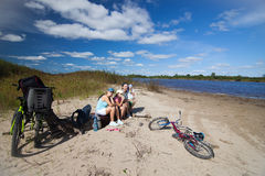 Family having a rest on a river coast Stock Photography