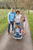 Family Having Ride In Wheelbarrow In Countryside Stock Photography