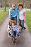 Family Having Ride In Wheelbarrow In Countryside Stock Images