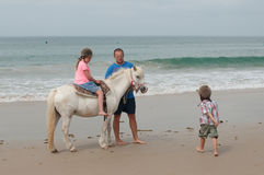Family having a riding lesson on a beach Royalty Free Stock Photography