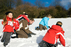 Family having a snowball fight. Family with kids having a snowball fight in winter on top of a hill in the snow royalty free stock photo