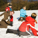 Family having a snowball fight. Family with kids having a snowball fight in winter on top of a hill in the snow stock photography