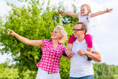 Family having summer walk on meadow outdoors Stock Image