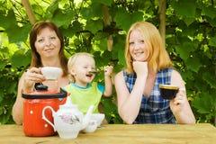 Family having tea  at pergola Royalty Free Stock Photography