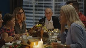 Family having Thanksgiving dinner at home. Family with children and grandparents gathering at table with candles and plenty of delicious food celebrating