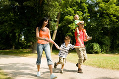 Family having a walk. Family with two kids having a walk in the park (focus is on the boy in front Stock Photography
