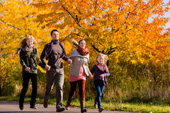 Family having walk in front of colorful trees in autumn Royalty Free Stock Photo