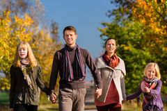 Family having walk in front of colorful trees in autumn stock image