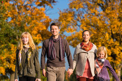 Family having walk in front of colorful trees in autumn Stock Images