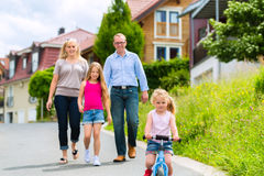 Family having walk in front of homes in village Royalty Free Stock Photo
