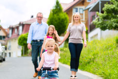 Family having walk in front of homes in village Royalty Free Stock Image