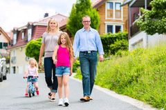 Family having walk in front of homes in village Royalty Free Stock Photos