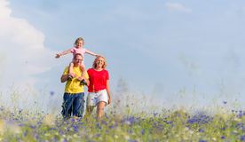 Family having walk on meadow with flowers Royalty Free Stock Image