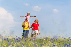 Family having walk on meadow with flowers Stock Images