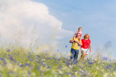 Family having walk on meadow with flowers Stock Image