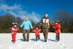Family having a walk in the snow Royalty Free Stock Photos