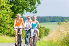Family having weekend bicycle tour outdoors Stock Images