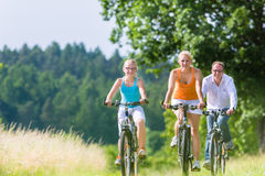 Family having weekend bicycle tour outdoors Stock Photo