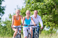 Family having weekend bicycle tour outdoors Royalty Free Stock Photo