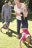 Family Having Wheelbarrow Race In Garden Together Royalty Free Stock Photos