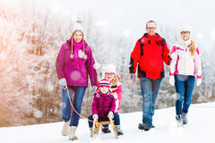 Family having winter walk in snow with sled Stock Photos