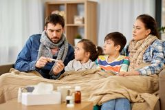 Family with ill children having fever at home stock images
