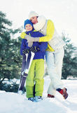 Family healthy lifestyle! Mother hugging son child with ski in winter forest Royalty Free Stock Image