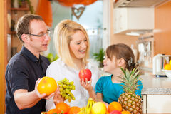 Family and healthy nutrition. Family (mother, father and child) with lots of fruits for breakfast food, this is healthy nutrition royalty free stock photo
