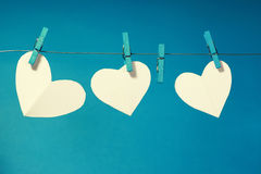 Family of hearts. Three paper hearts pegged on a line with a blue background. One heart is missing Stock Photo