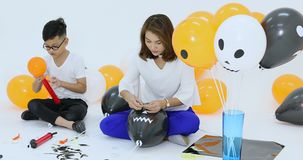 Family help together to prepare balloons. Group of people in family help together to prepare balloons of halloween party. Concept for happiness in festival stock video footage