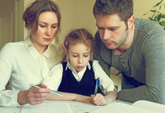 Family helping daughter with homework. Royalty Free Stock Image