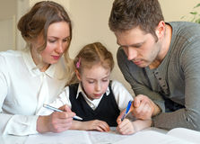 Family helping daughter with homework. Stock Image