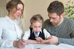 Family helping daughter with homework. Stock Photo
